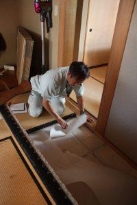畳を起こして、床下の状況を調べる菅谷監督。