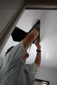 浴室の点検口から、給水管の流れを確認する菅谷監督。