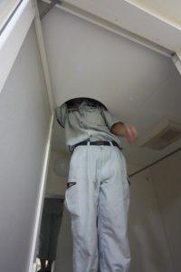 浴室の点検口からダクト・配線の状況を確認する河北現場監督