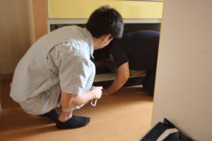 キッチンの流しの下の点検口から、配管を確認する半田アドバイザー。
