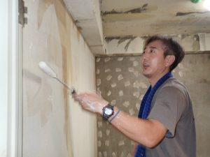 ローラーでコンクリートに塗っていく菅谷現場監督。